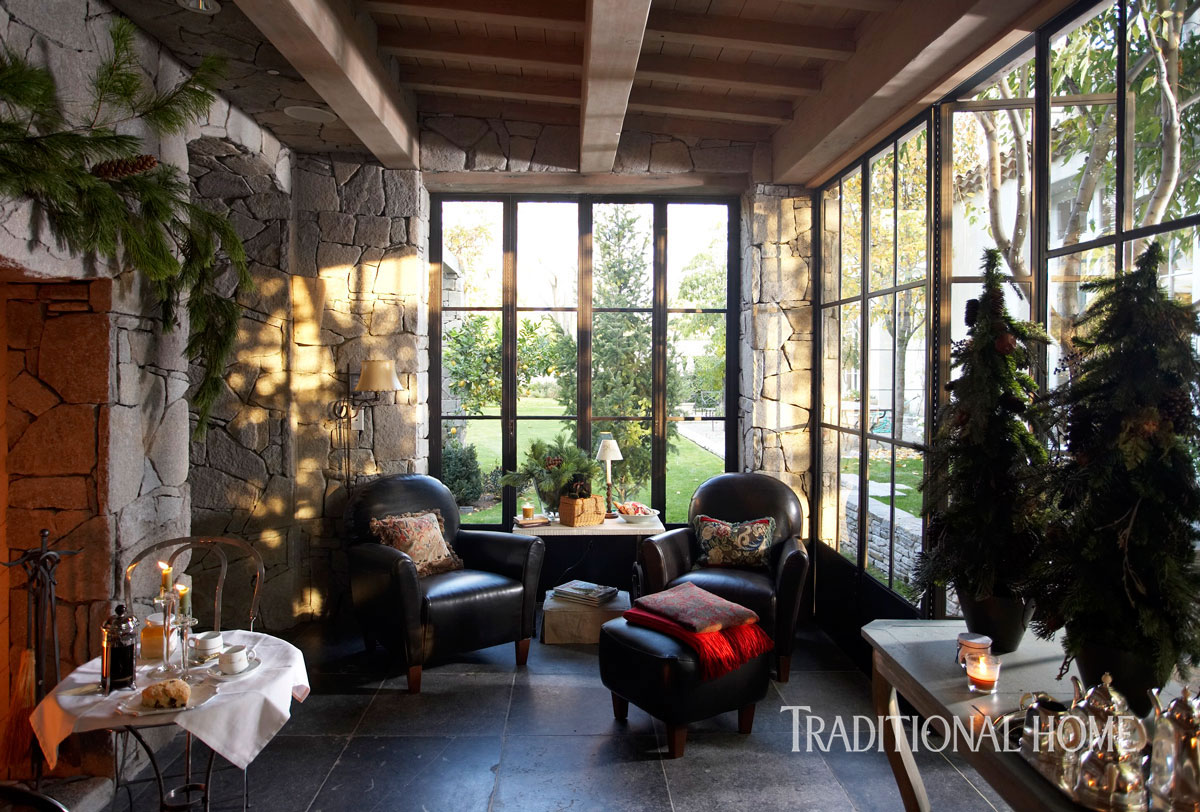 tall windows flood this porch with light while wooden beams stone walls and a gracious fireplace create plenty of charm simple greeneryabove the - Neutral Christmas Decor