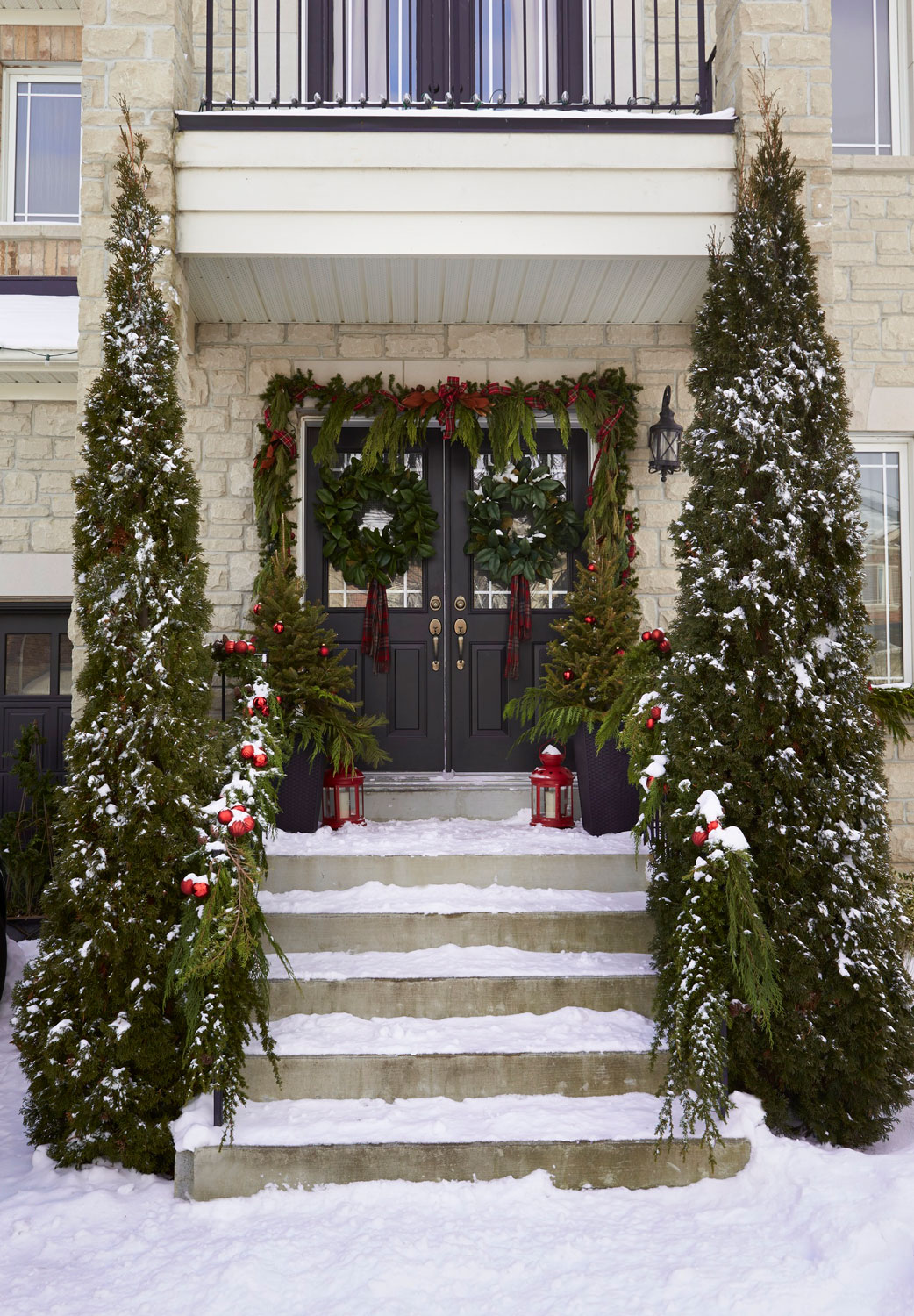 the classic red and green combination continues on the wreaths and the garland draping the doorway - Classic Outdoor Christmas Decorations