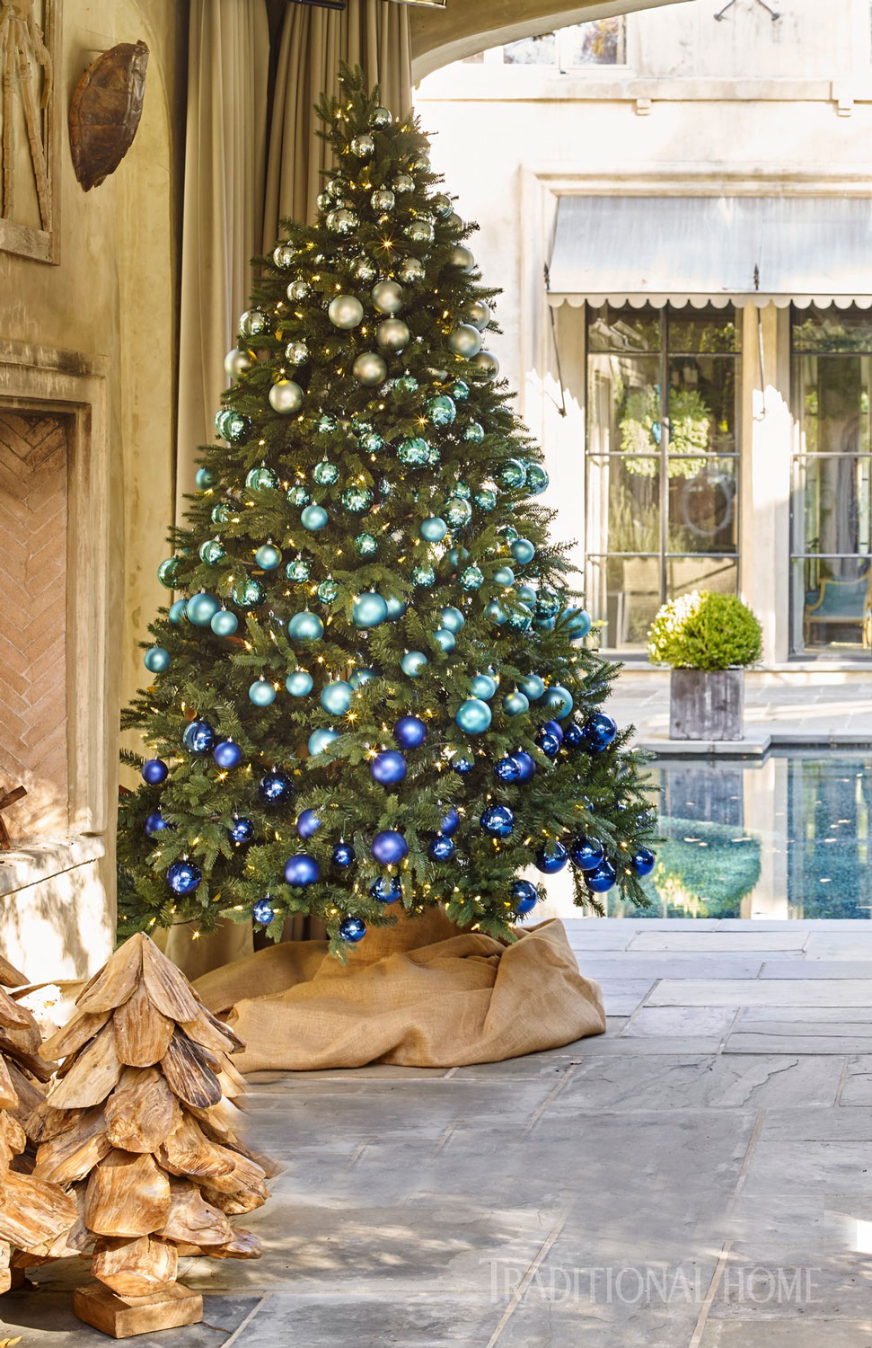 Christmas decoration with candles that spins - Shatterproof Ornaments In Shades Of Blue Lend An Ombr Effect To The Tree In This Outdoor Living Area The Colors Of The Ornamnets Mimc The Colors Of The