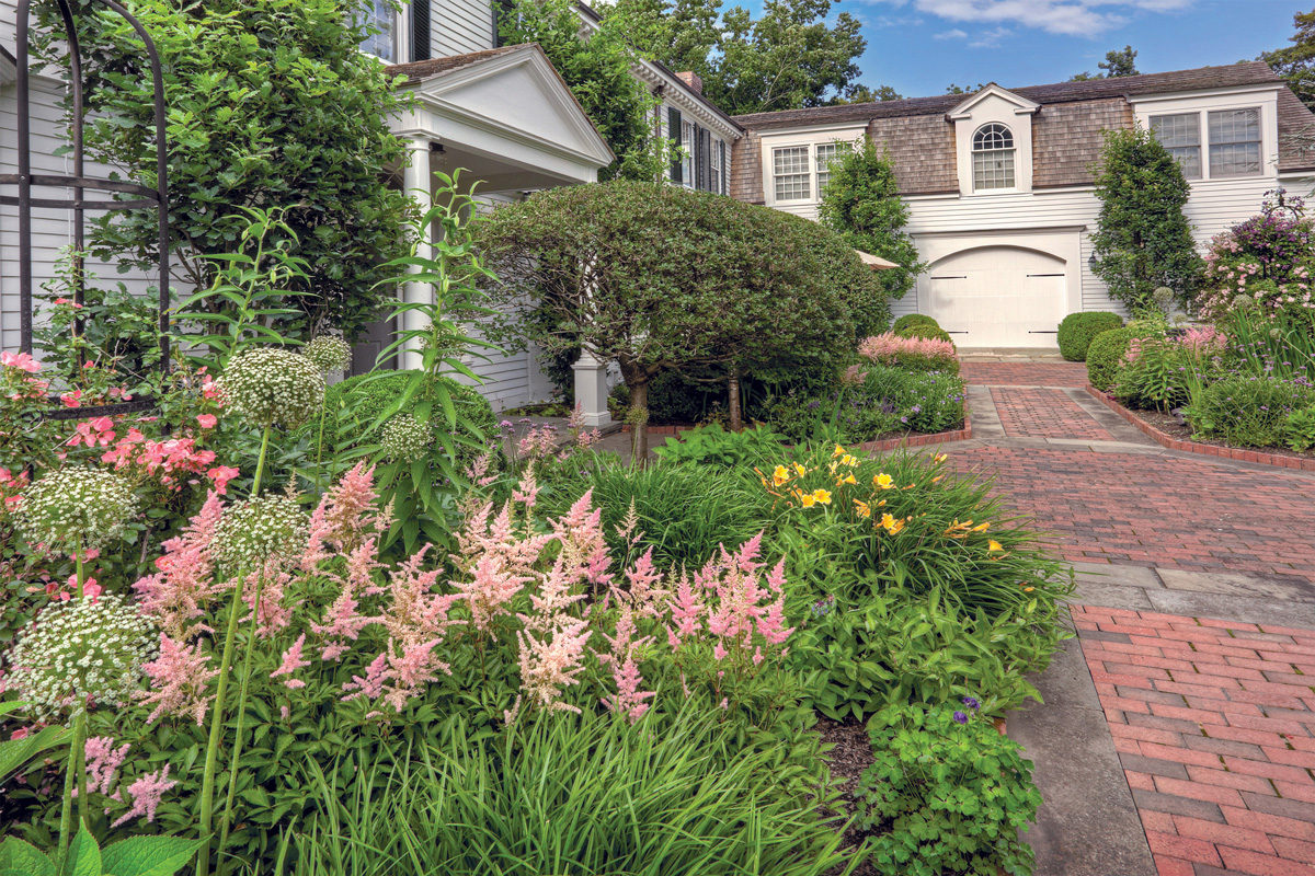 Plan a colorful perennial garden traditional home even though the white allium a late spring bloomer is about to fade in this garden the pink astilbe yellow stella de oro daylily capture the eye altavistaventures Images