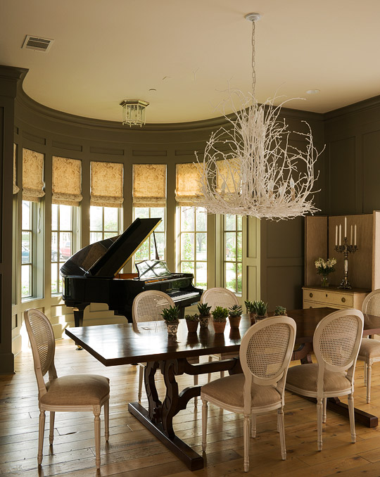 Silhouetted against a demilune bay window a glossy black piano provides a dramatic focal point for a dining room painted earthy green