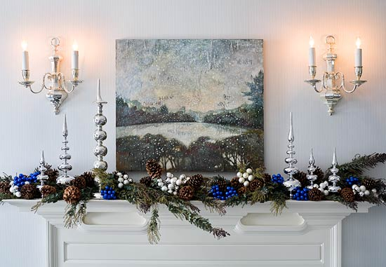 In a Massachusetts Colonial home, the master bedroom mantel is lined with fresh pine boughs, silver finials, and glass balls in blue and silver.