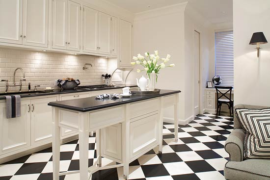 Black and white reign supreme in this kitchen, with checkerboard tiles laid  on the diagonal and black-and-white patterned fabric covering a nearby  chair.