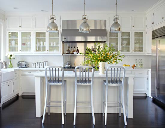 All White Kitchen With Black Floor White Scullery Type Cabinets Mingle With Glossy White Subway Tiles Marble Countertops And Stainless Steel Appliances To