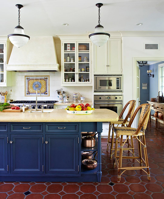 white walls and white painted cabinets recede against the rich navy blue painted surface of a kitchen island topped with creamy yellow marble