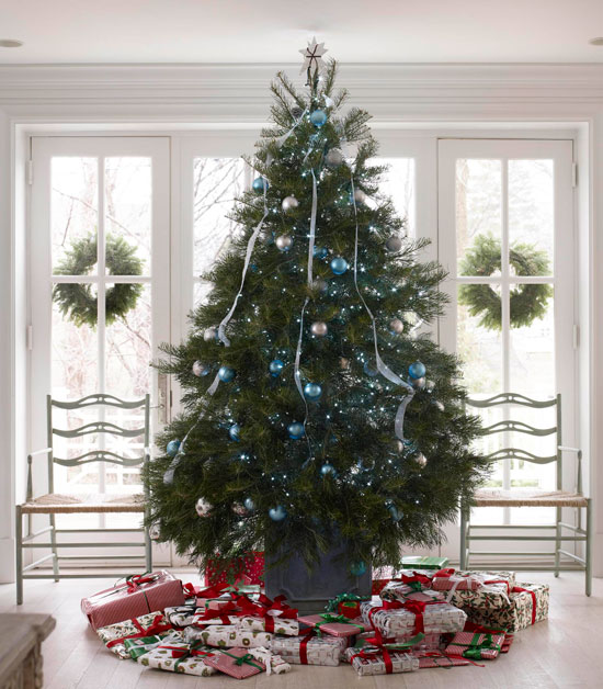 Here, a large white fir tree decorated simply in blue and silver ornamental balls with ribbon streaming from the top creates a classic Christmas atmosphere.