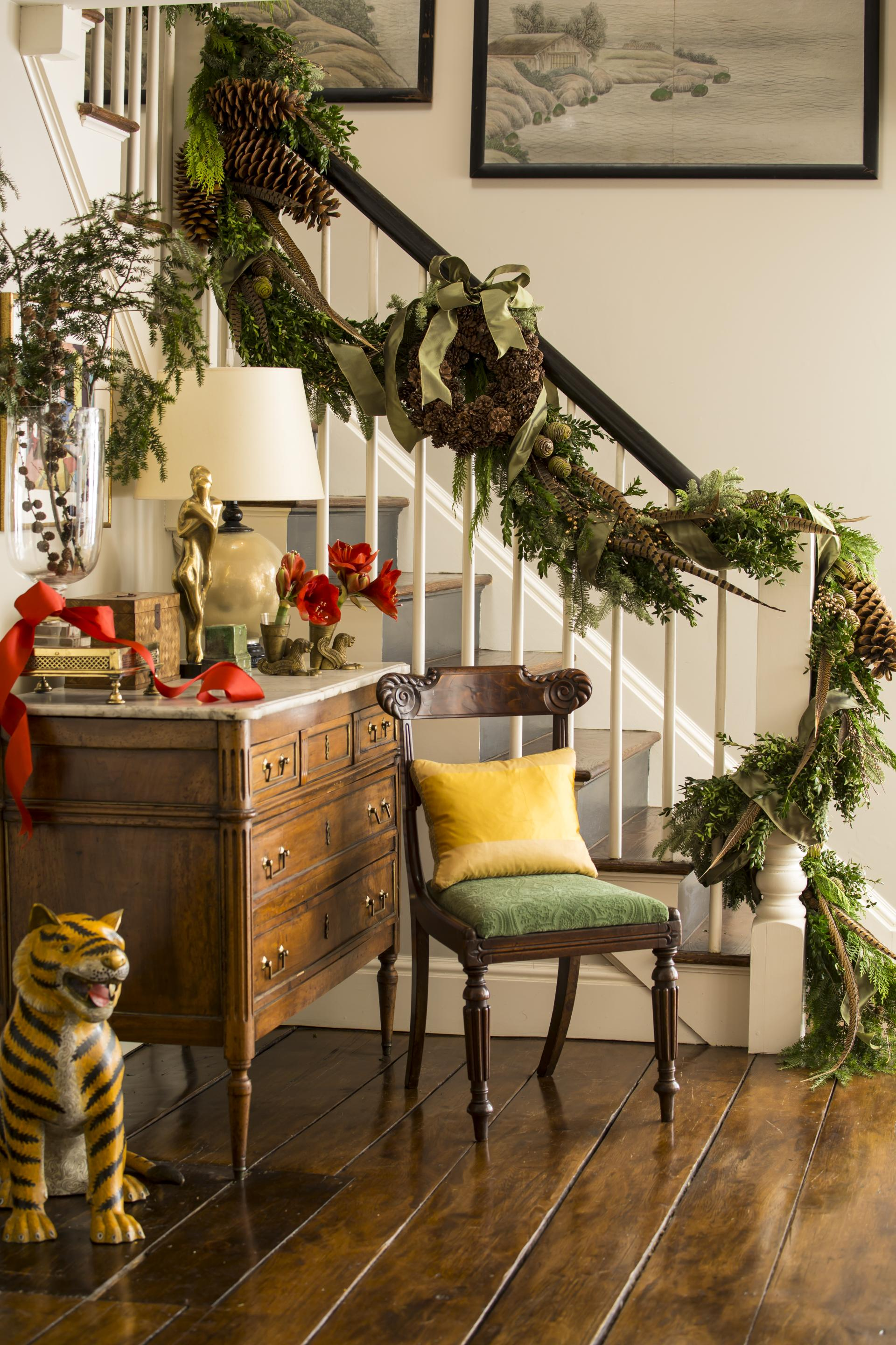 fresh greenery entwined with pheasant feathers pine cones and green ribbon adorn the banister of this stairway you can find the festive red with accents