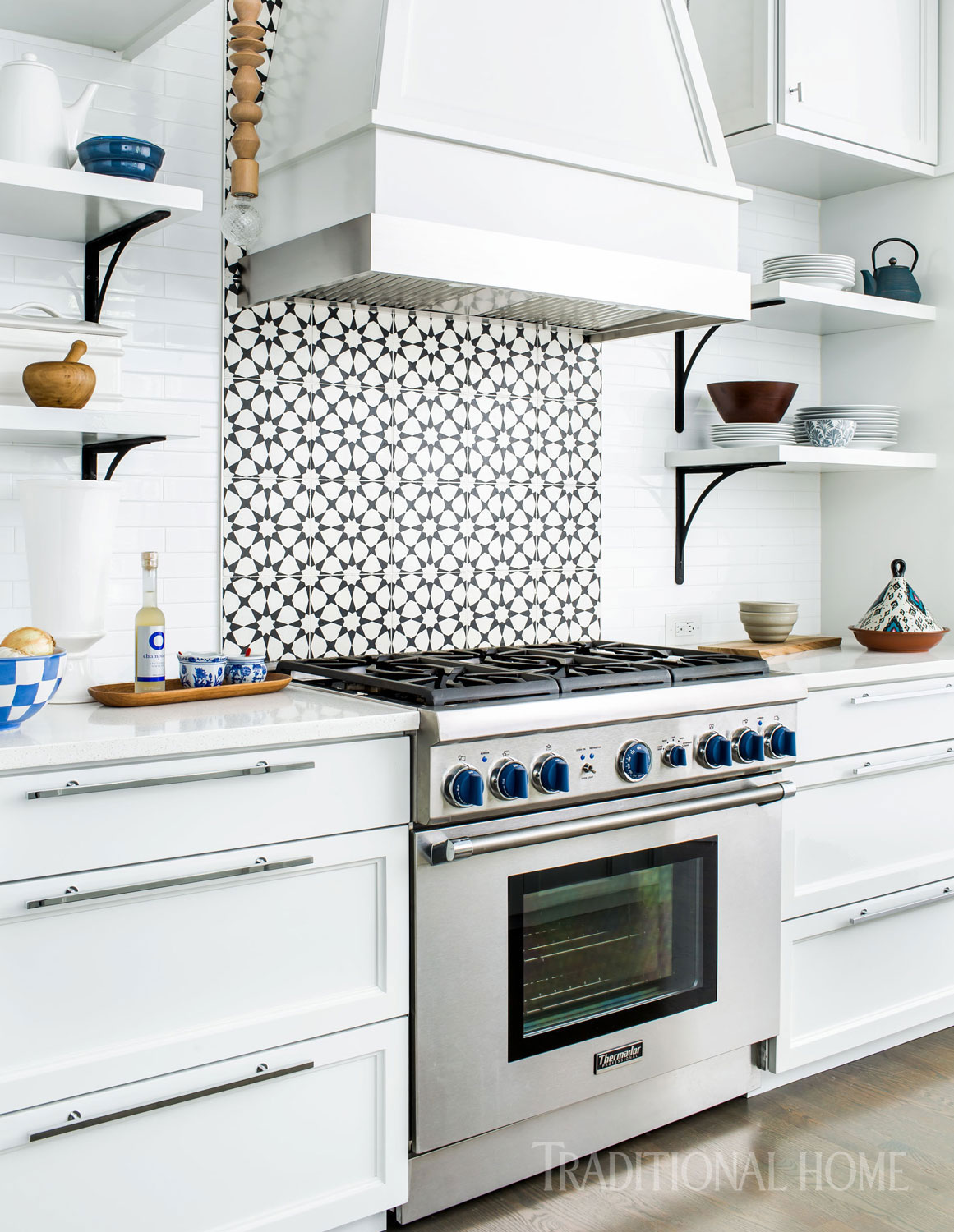 The custom vent hood above the Thermador range is mostly wood with a band of stainless steel closest to the heat. The patterned concrete backsplash tiles have color that goes all the way through. Come see 36 Best Beautiful Blue and White Kitchens to Love! #blueandwhite #bluekitchen #kitchendesign #kitchendecor #decorinspiration #beautifulkitchen