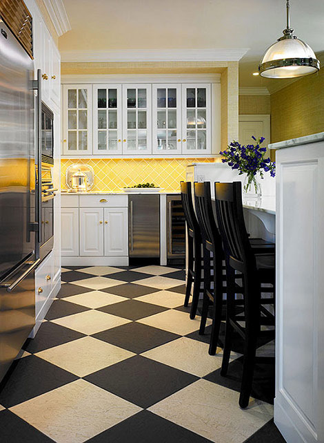 Warmed by taxi-yellow tiles on the backsplash and a black-and-beige  checkerboard tile floor, this mostly white kitchen is sleek but not cold.