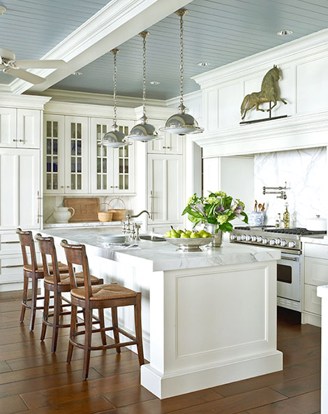 A blue-gray painted ceiling emphasizes the lakeside location of the home in  which this white kitchen resides. Thick white marble countertops, ...