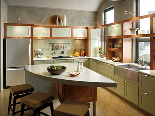 seating at a rounded triangular island allows people to converse with those in the kitchen or adjoining living area the kraftmaid cabinetry are putnam