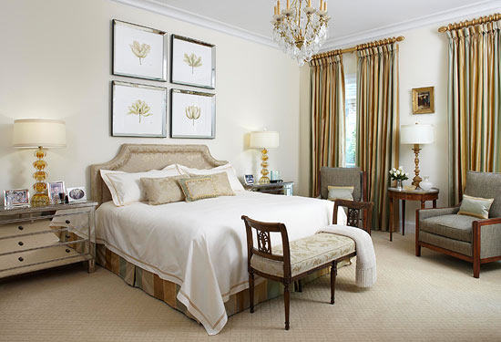 Hotel-style neutral bedroom with double bed, bedside table, footstool and  wall panel