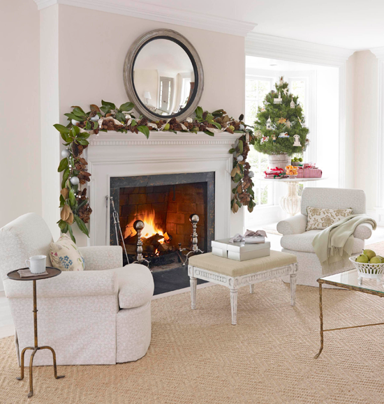 modest greenery above the mantel makes a beautiful impact on this living room bathed in white a large round mirror hanging above highlights the silver - Beautiful Mantel Christmas Decorations