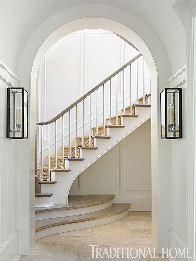Interior design ideas photo gallery and decorating ideas from a Phoebe Howard designed manor home. Matching curved stairways are tucked into opposite ends of the entry to make them less imposing. #interiordesign #staircase #traditional #classic