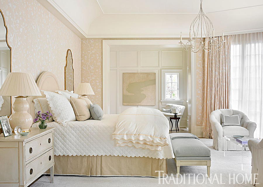 Classic and romantic bedroom design by Phoebe Howard.To add a hint of texture to the master bedroom's sleepy tranquillity, Howard upholstered the walls in the same tone-on-tone crewelwork embroidery she chose for the curtains. The headboard and bedskirt are in a creamy Calvin fabric that harmonizes with the walls, furthering the room's soothing appeal. Mirrors reflect the glow of bedside table lamps from Roy Hamilton. #bedroomdecor #traditional #romantic #whitedecor #interiordesign