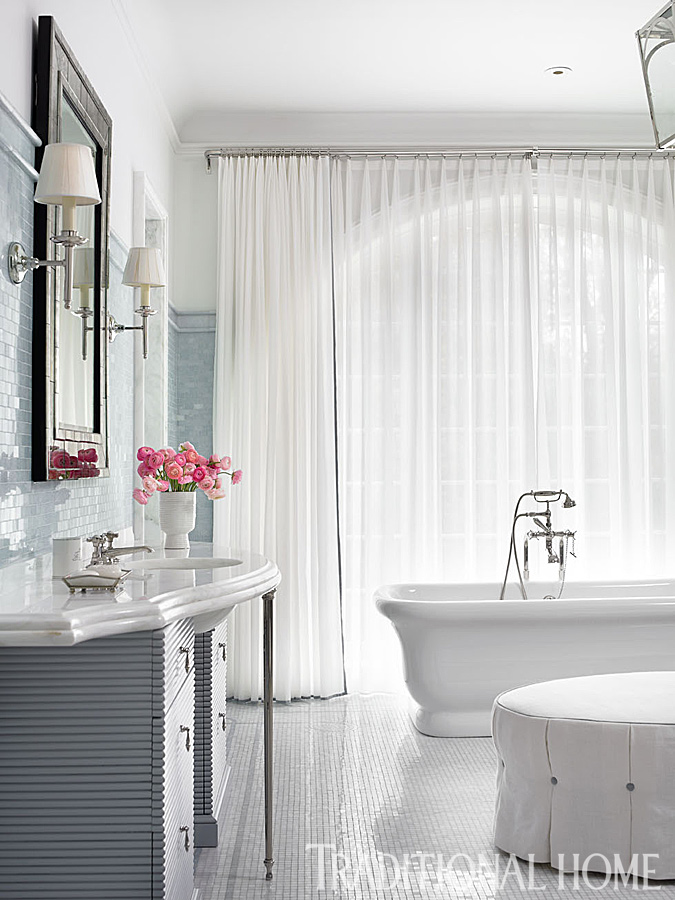 Classic bathroom design in a traditional home with interiors by Phoebe Howard. A Waterworks tub is set against an elegant backdrop of floor-to-ceiling curtains in a Pindler & Pindler acrylic fabric that's impervious to moisture. A painted vanity has decorative nickel legs from P.E. Guerin. #bathroomdesign #traditional #classic #luxurybath #waterworks