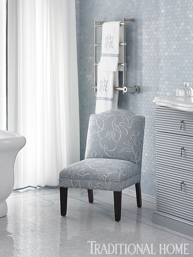 Soft blue bathroom decor in a traditional home with interiors by Phoebe Howard. Walls are sheathed in Blue Celeste marble tile from Renaissance Tile & Bath. The pattern of the Lee Jofa fabric on the chair echoes the curves in the mosaic floor-tile border. #bathroomdecor #blue #marbletile #interiordesign #classic