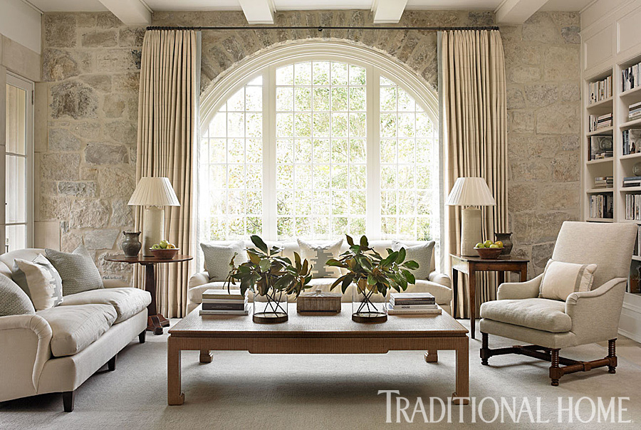 Interior design by Phoebe Howard in a family room where luminous stone walls make an indoor appearance. A floor-to-ceiling array of limestone outlines a beautiful arch of glass and greenery and dominates one end of the room. #familyroom #interiordesign #traditional #classic #neutrals