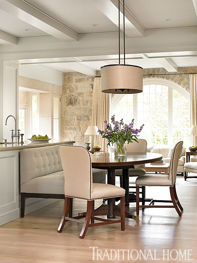 Breakfast area of a classic kitchen designed by Phoebe Howard. A light fixture from John Rosselli illuminates a custom-made kitchen table and Hickory Chair seating. #interiordesign #breakfastroom #classic #traditional