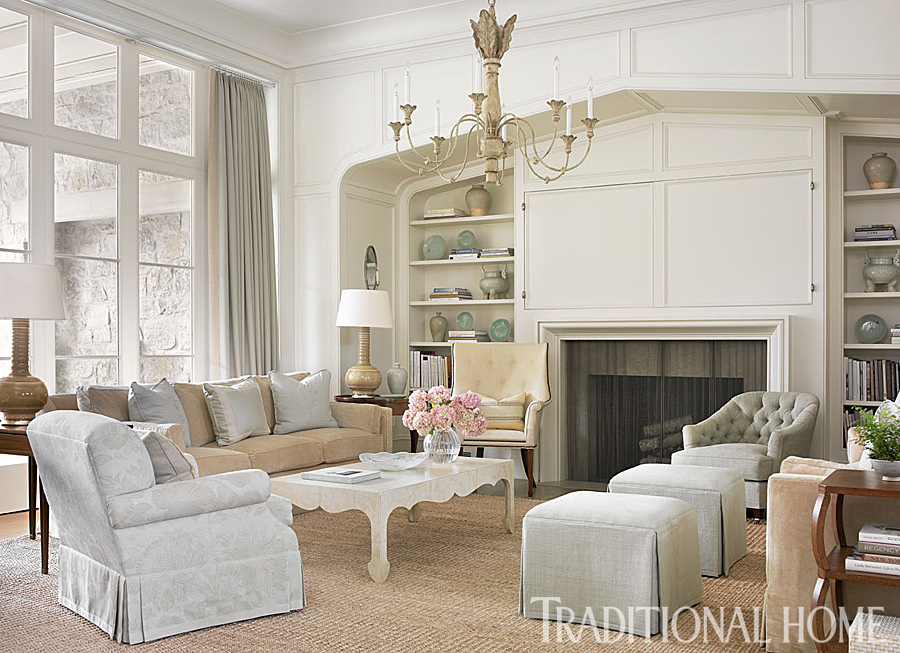 Interior design inspiration from Phoebe Howard. The living room's soaring ceiling is brought down to a more intimate scale with a chandelier from Ainsworth-Noah. A tufted chair covered in a subtle fabric from Kravet and a club chair in a TylerGraphic print add bits of misty blue to the neutral tones. #livingroom #traditional #interiordesign #classic #whitedecor