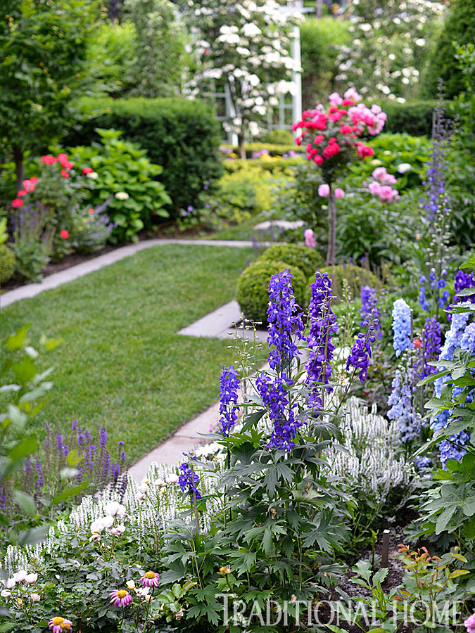 Perennial beds filled with delphiniums, hollyhocks, and viburnum line the charming pass-through that connects the entry garden to backyard areas, including a bluestone patio. Lines of stone pavers give the space a formal air.