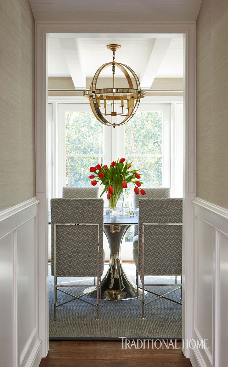 Dining room with Mid-century modern round dining table and mother of pearl pendant. Traditional Home Tour Renovation by William Hefner. #diningroom #traditional #seagrass #wallpaper