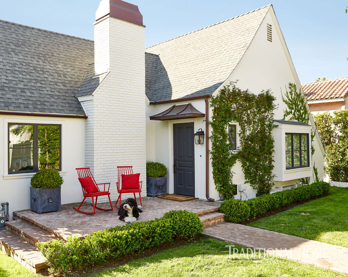 Beautiful curb appeal and outdoor inspiration from a front porch with red rocking chairs. #traditional #houseexterior #frontporch #redwhiteblue