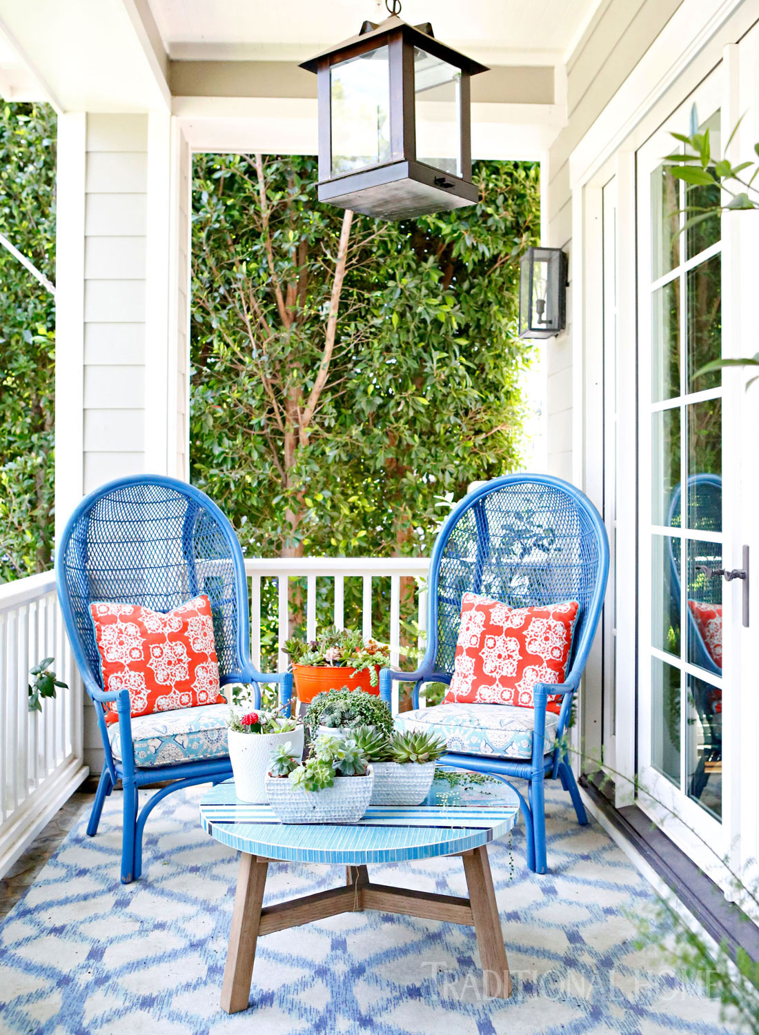 Cheerful red, white, and blue decor on a charming porch. Vintage wicker chairs shine in a new blue finish. Vibrant pillows extend the orange accent that weaves through the house. #porchdecor #redwhiteblue #americana #traditional