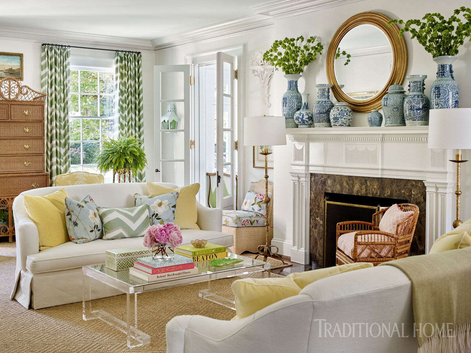 "Two ""Catherine"" sofas from Century Furniture flank a fireplace that's painted, along with the walls, in Benjamin Moore's ""Simply White."" The mantel is lined with homeowner Bunny Blackburn's collection of blue-and-white Chinese porcelain vases and jars. Designer Sarah Bartholomew added a touch of airiness with an acrylic cocktail table from Interlude Home. The wicker highboy is vintage Ralph Lauren for Henredon; the rattan chair is also a vintage find."