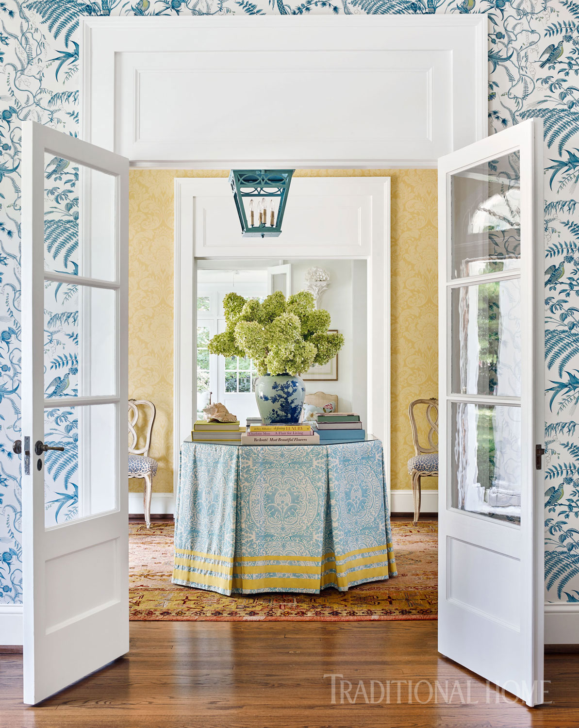 "To soften the formal look of the entryway's yellow damask wallpaper, Bartholomew mixed in more casual fabrics, including Quadrille's ""Veneto"" fabric in Venice Blue, which covers the center hall table. Fresh yellows and blues thread throughout the palette of the entire home."