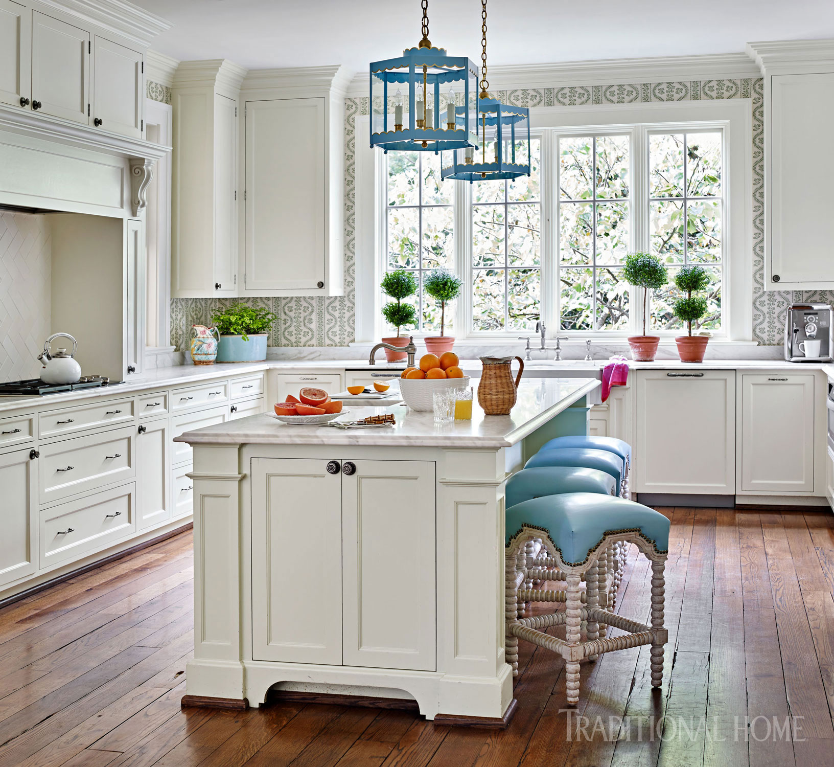 Quiet blues on upholstery and the Coleen & Company scalloped hanging lanterns dot the all-white kitchen.