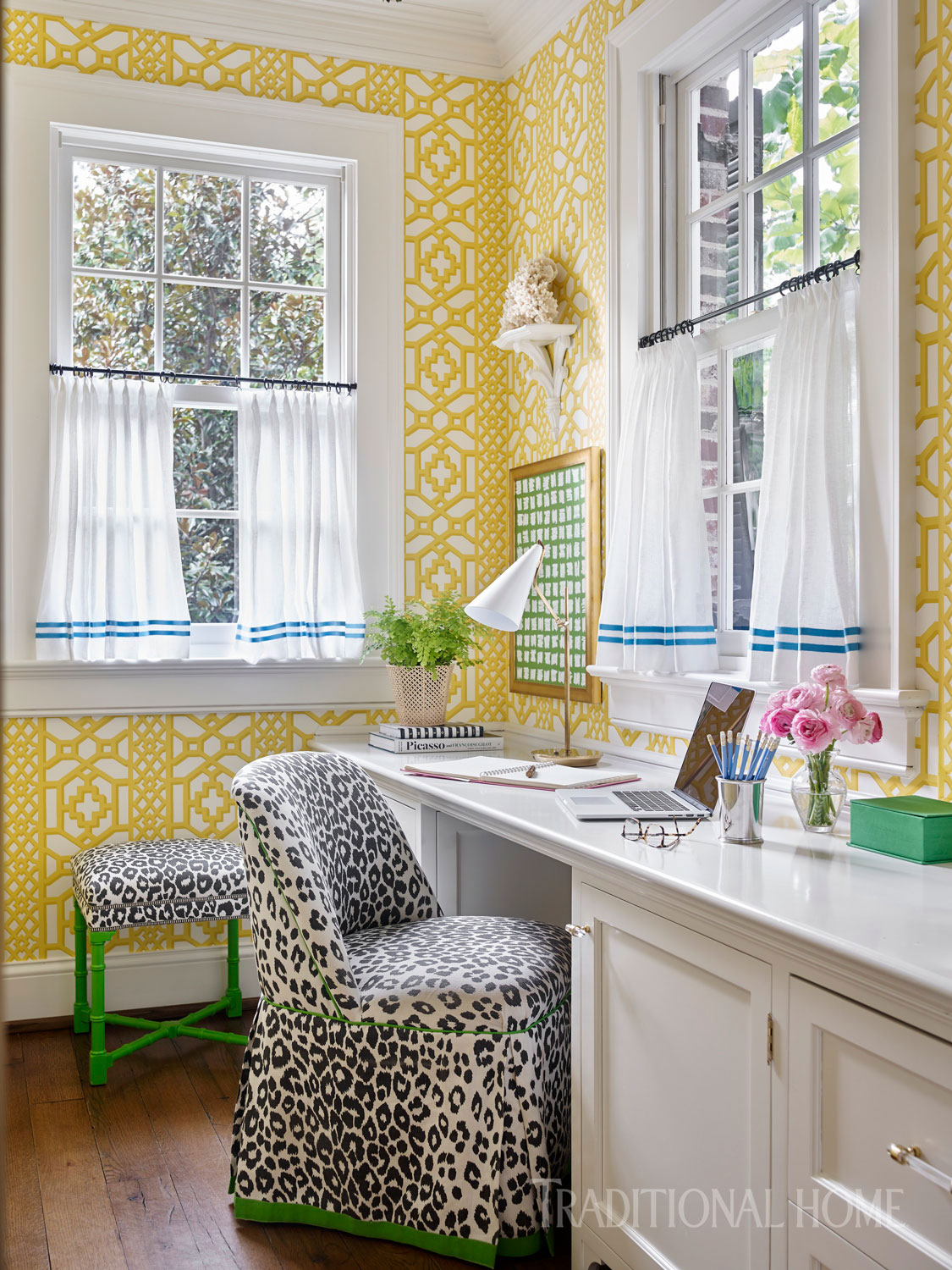 Yellow wallpaper wraps this work space in cheer. Black-and-white cheetah print fabric is paired with green trim on a skirted chair and green legs on a coordinating stool.