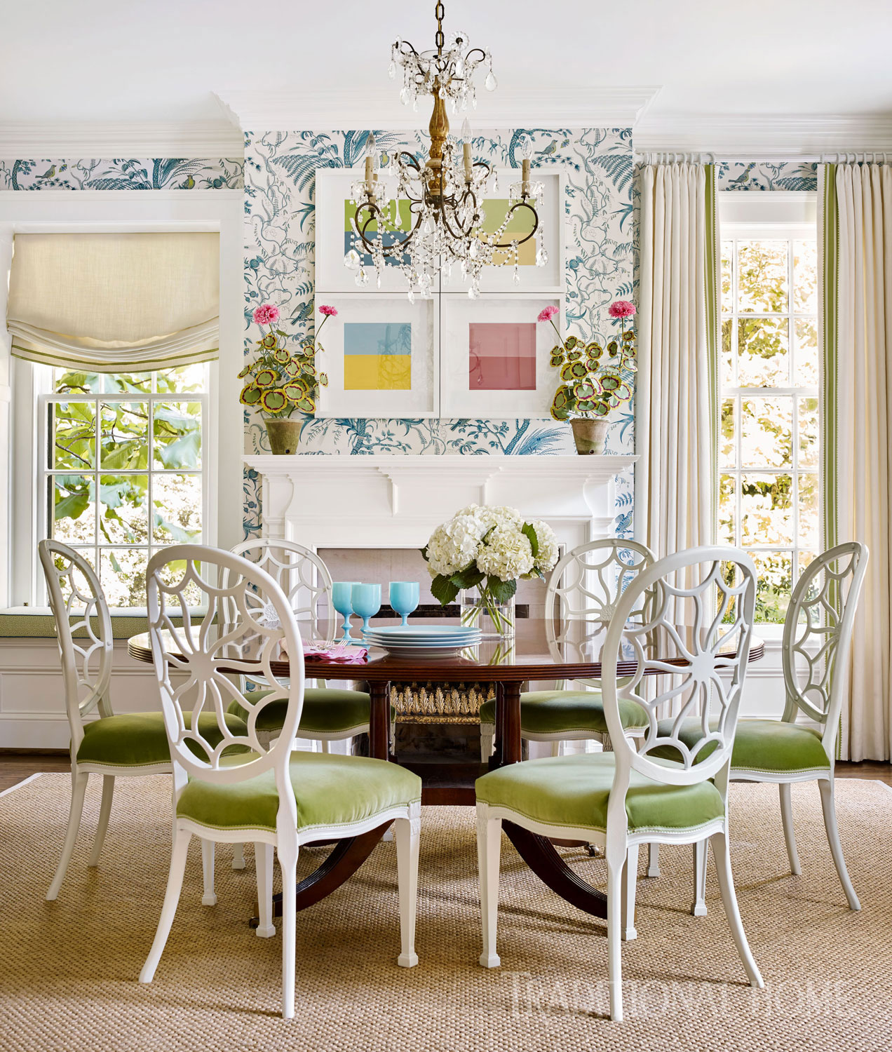 "he Brunschwig & Fils ""Bird and Thistle"" wallpaper in blue plays nicely with apple green velvet on Hepplewhite-inspired dining chairs. Delicate paper flowers from The Green Vase pop against a grouping of contemporary pieces, A Color Study, by Janet Porcher Gregg."