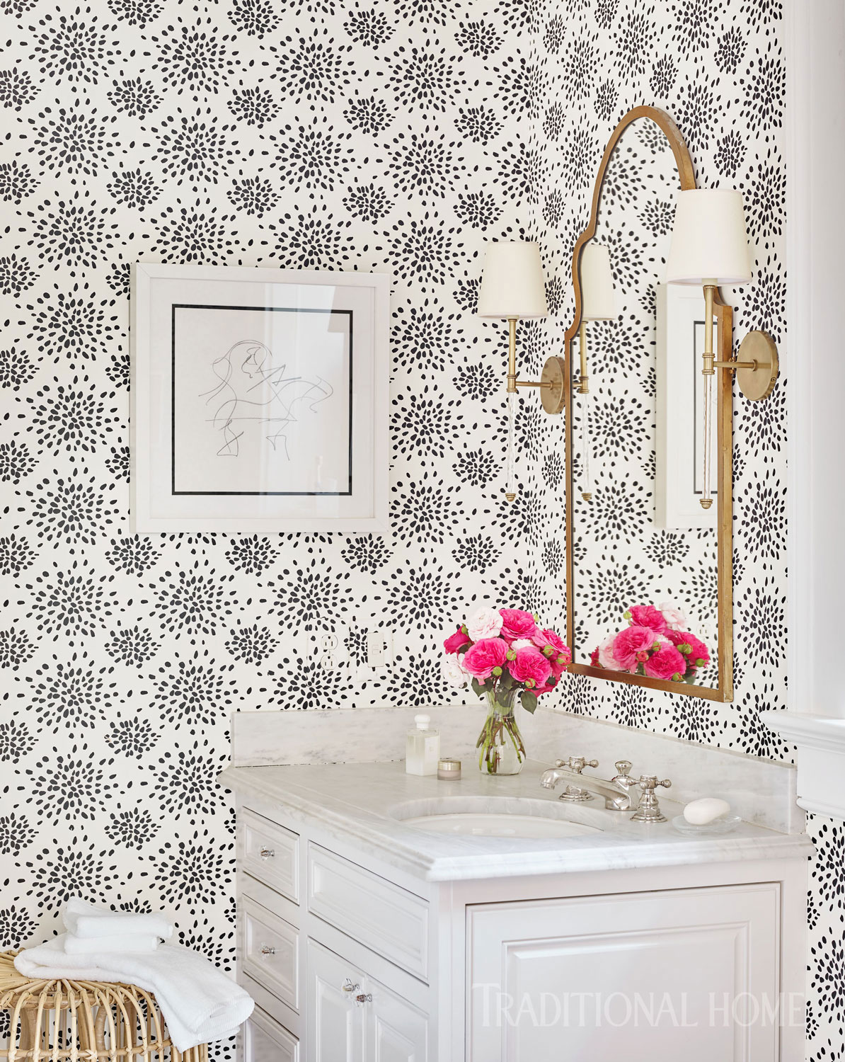 "The Albert Hadley ""Fireworks"" wallpaper sets a graphic black-and-white backdrop for Clare's bath. But warm golds in the sconces and mirror dial down the drama."