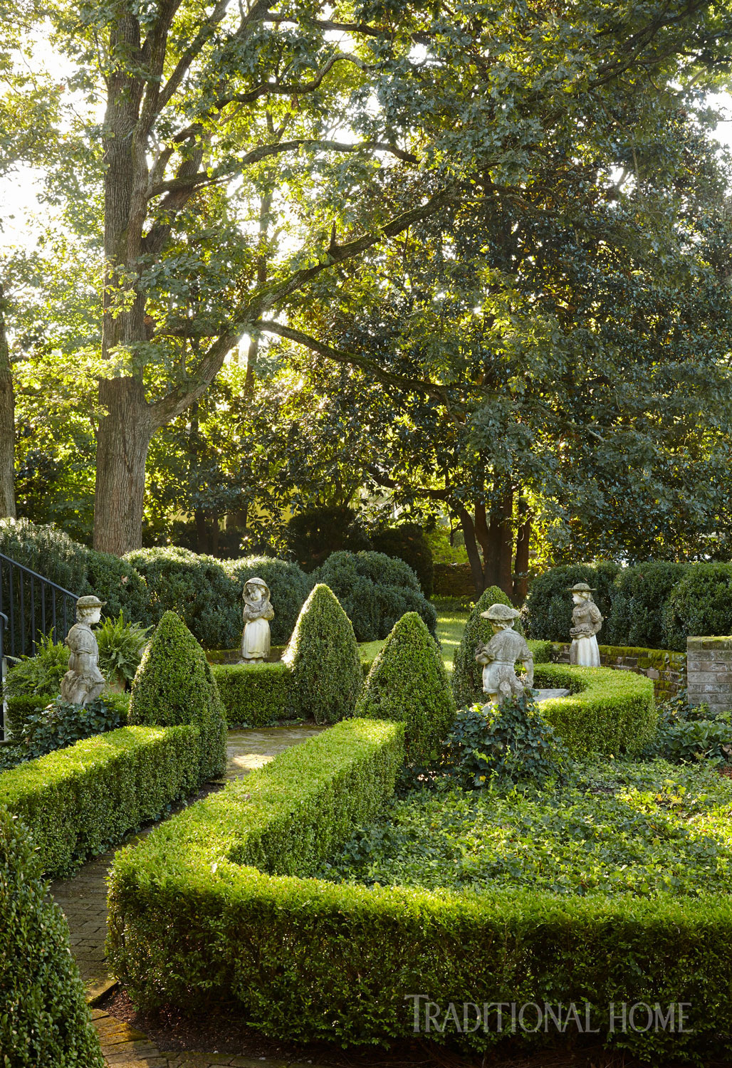 A charming garden path is framed by neatly trimmed boxwood hedges.