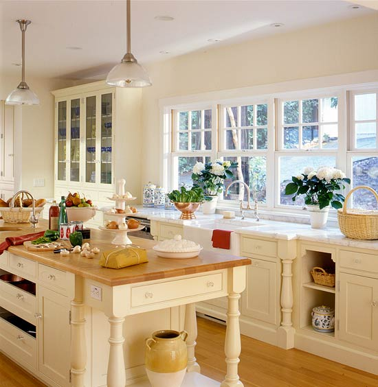 Gleaming Expanses Of Wood Both On The Island Top And Floor Add Warmth To A Kitchen Decked Out In Creamy White Painted Cabinets With Beaded Details