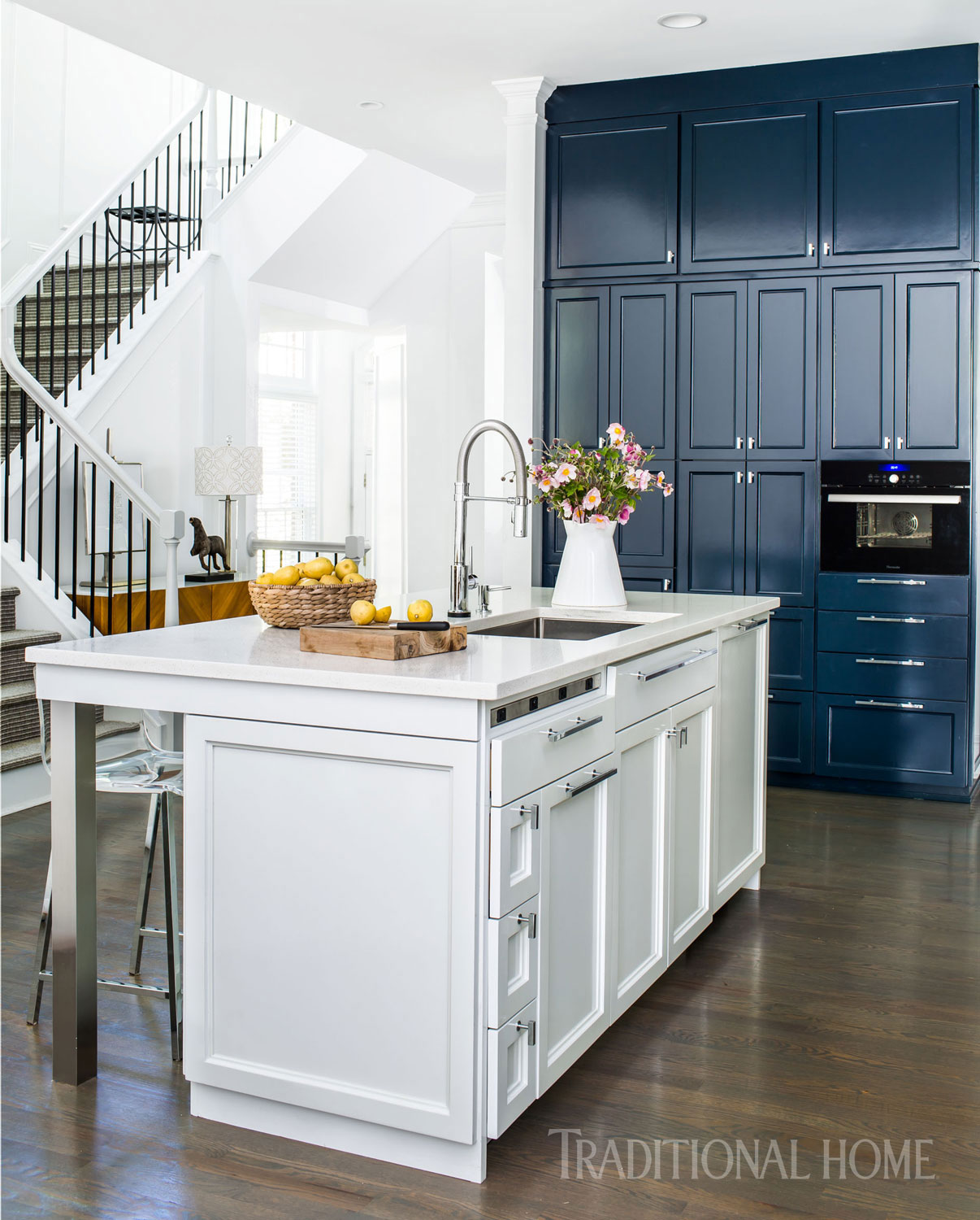 A 12-foot-tall wall of blue cabinetry echoes the backsplash color and allows a black Thermador steam oven to almost disappear. Come see 36 Best Beautiful Blue and White Kitchens to Love! #blueandwhite #bluekitchen #kitchendesign #kitchendecor #decorinspiration #beautifulkitchen